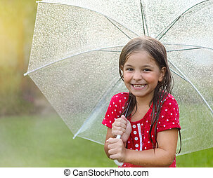 Child with wearing polka dots dress under umbrella