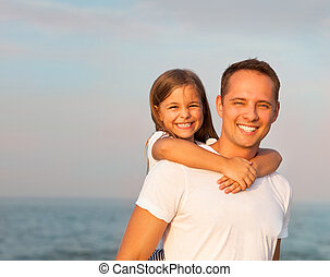 Happy young father and his daughter playing on the beach