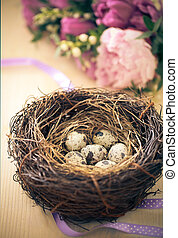 Flowers and easter nest with eggs on rustic wooden...