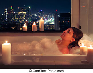 Relaxed woman in bathroom with candles