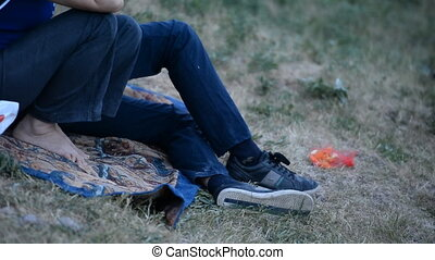 Rest in the park in the open air, legs in jeans clothes