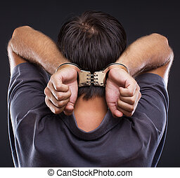 Man in handcuffs on gray background - Man in handcuffs with...