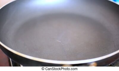 pouring oil into the steaming pan and filling threaded ham cubes for frying. HD. 1920x1080
