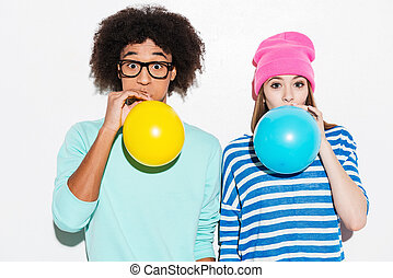 Double bubble love. Funky young couple inflating balloons...