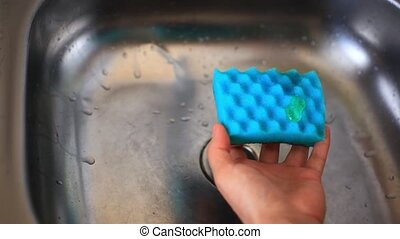 hands with sponge washing dishes impregnated With detergent...