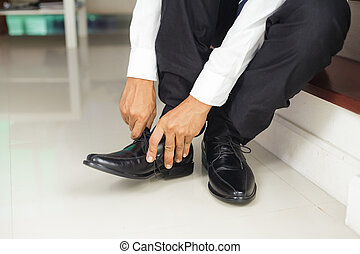 Man tying shoes indoors