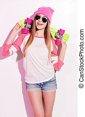 Happy skater girl Playful young woman in pink headwear and...