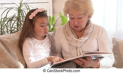 Grandmother reading a book with her granddaughter, while...