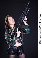 Portrait of a woman in a military uniform with an assault rifle