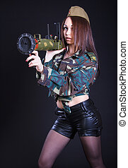 Woman in the military uniform with a grenade launcher over...