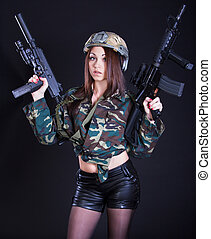 Woman in the military uniform with assault rifles over black...