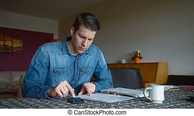 Man calculating Bills at home - Man at home calculating the...