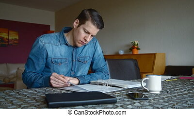 Man calculating Bills in Living Room - Man at home...