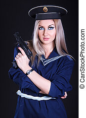 Woman in the marine uniform with a gun over black background