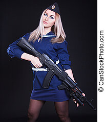 Woman in the marine uniform with an assault rifle over black...