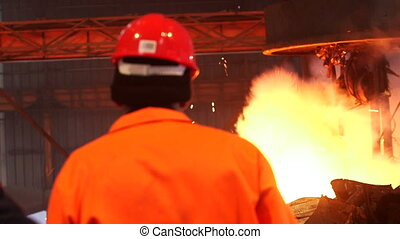 Worker controlling smelting iron - factory Hard work in the...