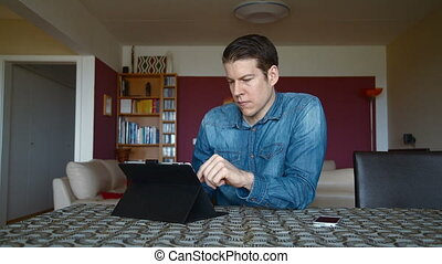 man receiving good news at home - man at home with tablet...