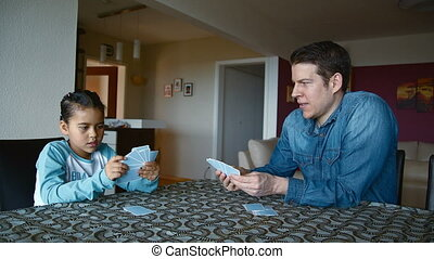 Happy young girl playing cards - father and daughter playing...