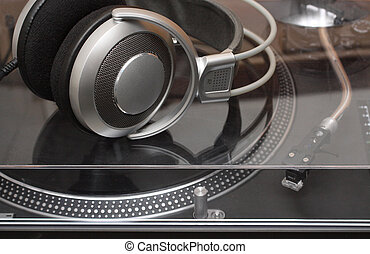headphones on gramophone disc player - silver headphones on...
