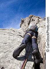 View from below of a climber while climbing a steep rock wall