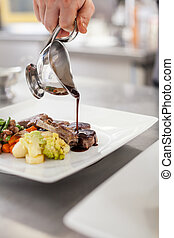 Chef plating up food in a restaurant pouring a gravy or...