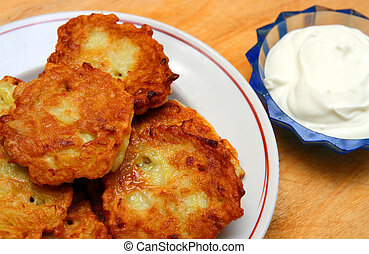 potato pancakes with sour cream - potato pancakes on plate...