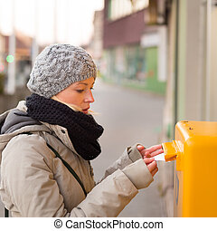 Young lady posting letters. - Young woman posting a letter,...