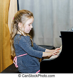 Cute little girl playing grand piano in concert hall
