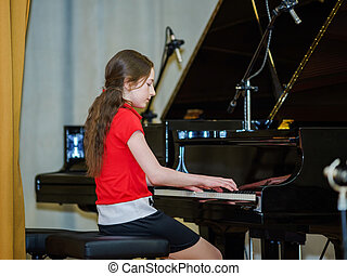 Teenage girl playing grand piano in concert hall