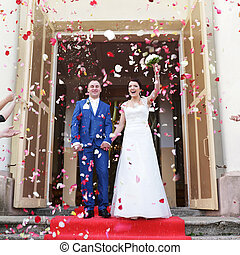 couple of newly wed showered with rose petals