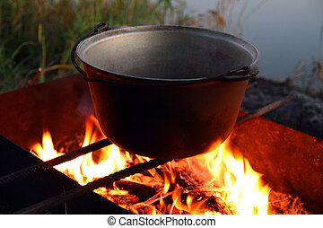 kettle over campfire near the river
