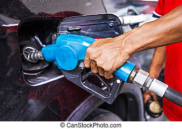Man refilling the car with fuel at a gas station
