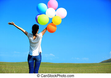 young asian woman with balloons - young asian woman on green...