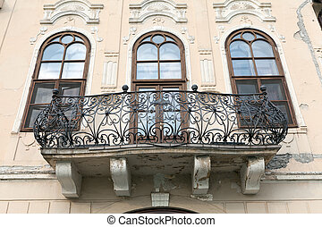 Balcony on a castle with three windows and the wrought iron bani