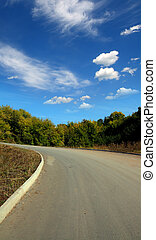 curved road uphill under blue sky with clouds