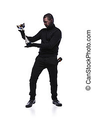 Thief in black mask - Thief in action carrying a trophy with...