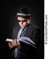 Seriously teenage boy dressed in suit reading book, isolated...