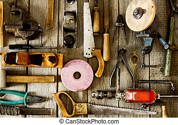 Many old working tools ( plane, saw, pliers and others) on a...