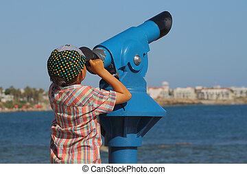 boy looking through a telescope
