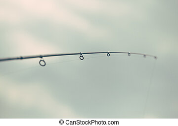 Fishing rod - Detail of a fishing rod over sky background.