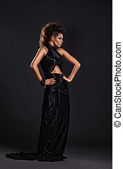 Woman in black long dress over dark background