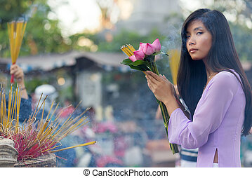 Vietnamese woman praying at temple, holding incense sticks...