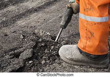 Road repairs - Man repairing the road with a pneumatic...