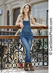 Portrait of a young girl in denim overalls - Portrait in...