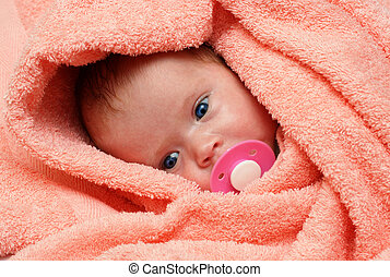 newborn baby with soother in peachey blanket