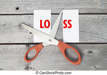 Cut loss concept against a wooden background