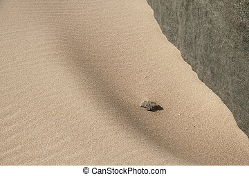 Outcast - Rock cliff against beach sand with ripples and...