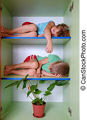 tired kids in a closet - two 5 year old kids sleeping on...