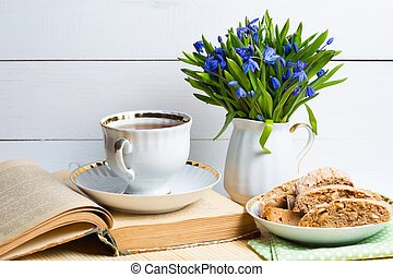 snowdrops in a vase, a cup of tea and biscotti on the table...