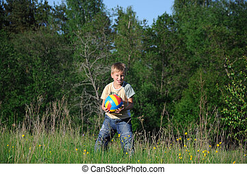 little boy with a ball in the park